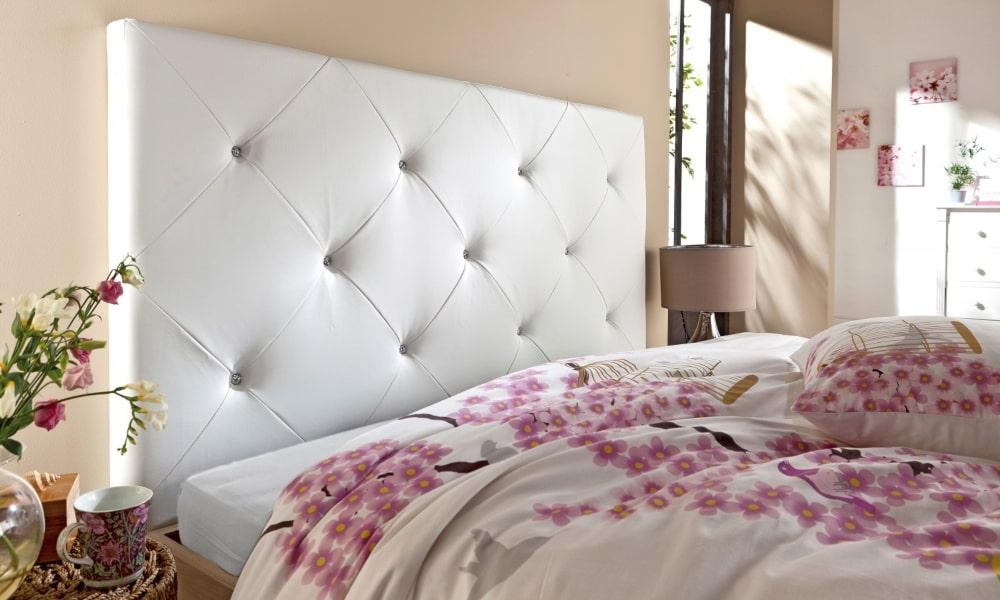 cama con cabecero blanco y edredón de flores