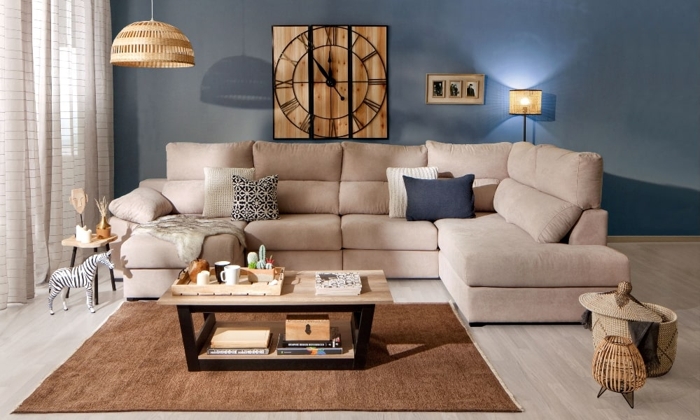 combinar cojines en un sofa beige en salon de paredes azules