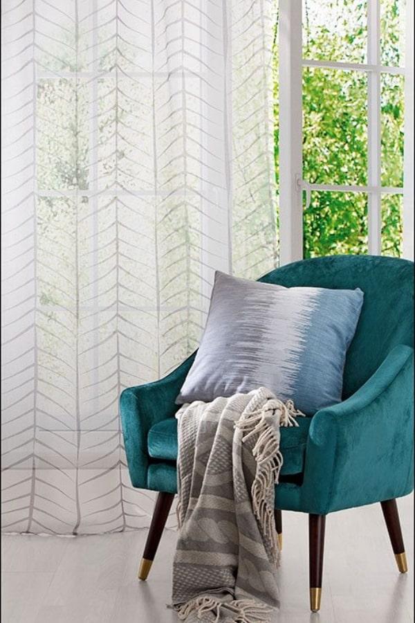 casa autosuficiente cortina blanca y sofá en terciopelo azul